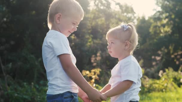 Happy family: little boy a and girl brother and sister hold hand on nature happy children concept. children look into each others eyes slow motion video. childhood kids play lifestyle