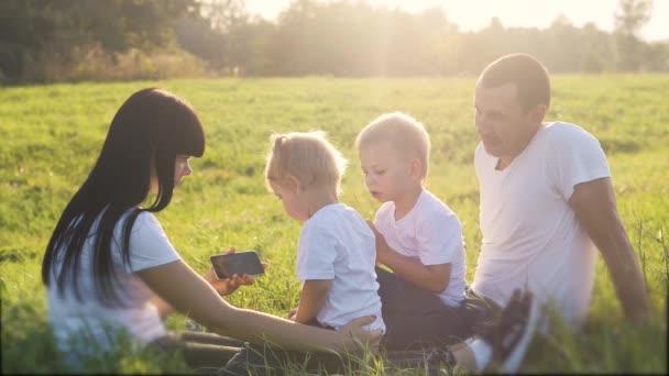 boldog családi csapatmunka okostelefon ülni fű játszani lassított felvétel. anya apa lánya és fia játszanak a fű természet a parkban napfény vicces. kis apa fiú játék internet digitális telefon