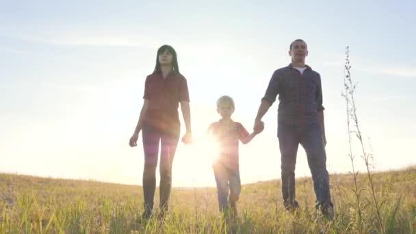 šťastný rodinný otec syn a máma jít zpomalit video koncept. šťastný týmová práce táta muž maminka dívka a syn chlapec dítě držet ruce chůze jít na hřiště v přírodě. šťastný životní styl rodina bezstarostné dětství