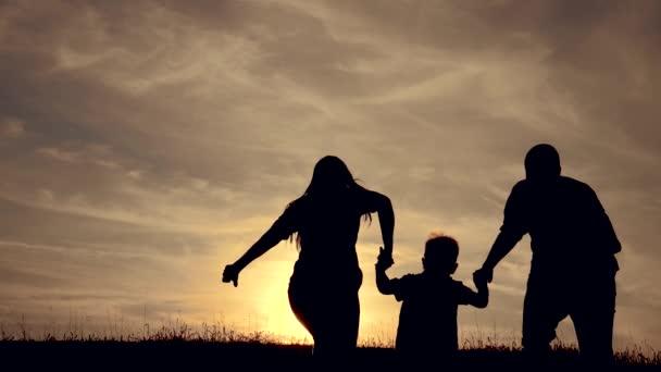 Šťastná rodina vtipné jít pro běží týmová práce Silueta, šťastné děti s matkou a otcem, rodina při západu slunce. Máma táta a syn stojí chůzi běžci na okraji útesu kopce sledování