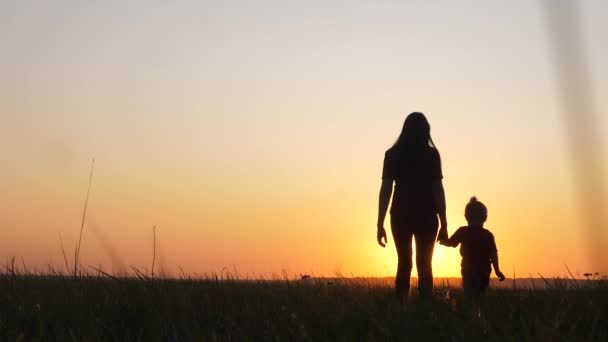 happy family a mom and daughter sunset silhouette in the park walking go slow motion. little girl and woman mom lifestyle hold hand walk go the field outdoors. happy family mom takes care of daughter