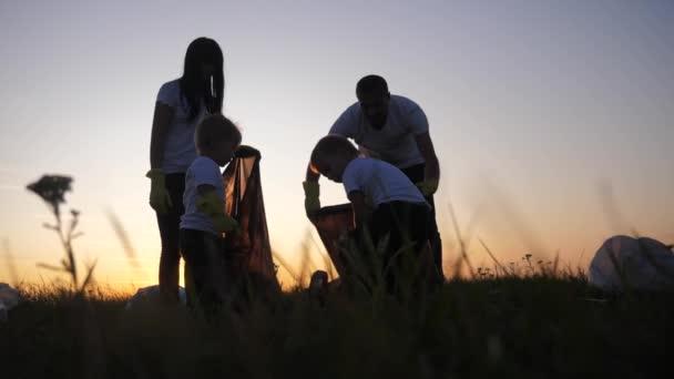 Umwelt Teamwork eine Ökologie Teamwork Freiwillige Bewusstsein Umweltverschmutzung Hausmüll-Konzept. Menschen Gruppe glückliche Familiensilhouette auf dem Sonnenuntergang Lebensstil sammelt Müll Plastik- und Papierabfälle