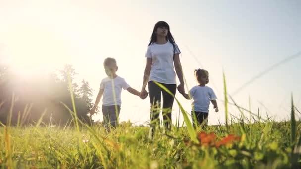 Šťastná rodina legrační chůzi jít za ruce týmová práce Silueta. šťastné děti malý chlapec a dívka s matkou rodiny při západu slunce. maminka a syn maminka lifestyle dcera a syn v bílý trička