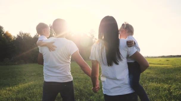glückliche Familie lustige Spaziergänge gehen für sind Händchen halten eine Teamwork Silhouette. glückliche Kinder Vater und kleine Junge Mädchen mit Mutter Familie bei Sonnenuntergang. Mutter papa und sohn gehen mutter tochter und sohn im weiß t