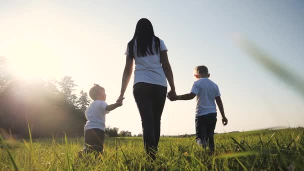 happy family funny walking go for are hold hands a teamwork Silhouette. happy children little boy and girl with mother family at sunset. mom and son mom daughter and son in white t-shirts walk on the