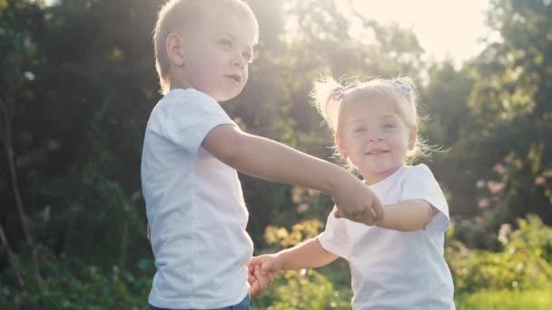 Šťastná rodina: malý chlapec a dívka bratr a sestra držet ruku v přírodě šťastný děti koncept. děti se do sebe dívají očima zpomalené video o životním stylu. dětské děti si hrají