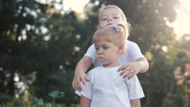 Šťastná rodina: malý chlapec objetí krouží objetí a dívka bratr a sestra držet ruku na přírodě šťastný děti koncept. děti šťastný rodinný chlapec objetí dívka životní styl zpomalení videa. děti dětství