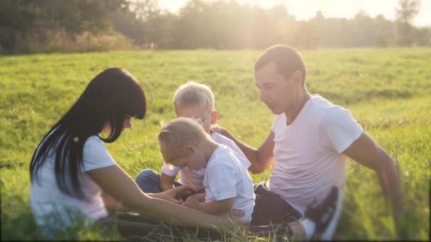 boldog családi csapatmunka okostelefon ülni fű játszani lassított felvétel. anya apa lánya és fia játszanak a fű természet a parkban életmód napfény vicces. kis apa fiú játék internet digitális