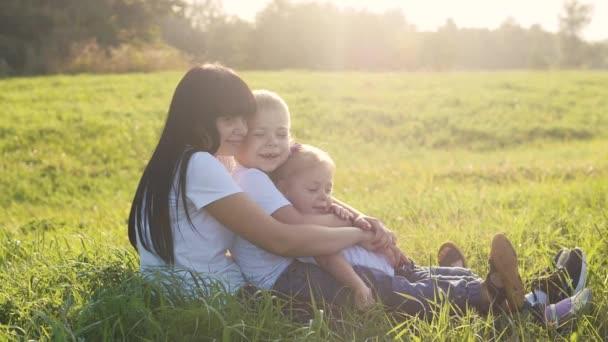 šťastná rodina týmová práce sedět na trávě hrát zpomalený film. Matka dcera a syn hrát na slunci tráva příroda v parku legrační.