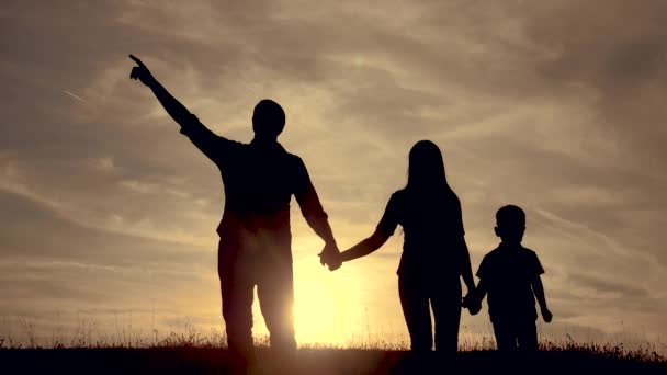 happy family lifestyle go for a walk a teamwork Silhouette ,happy children with mother and father , family at sunset . mom dad and son stand walking on the edge of a cliff of a hill watching the