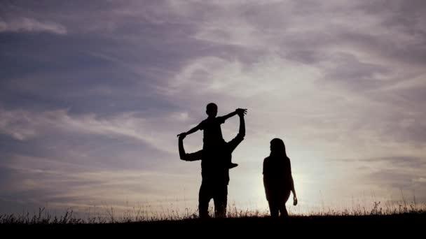 šťastná rodina jít na procházku týmová práce Silueta, šťastné děti s matkou a otcem, rodina při západu slunce. Máma táta a syn stojí na okraji útesu kopce a dívají se na západ slunce