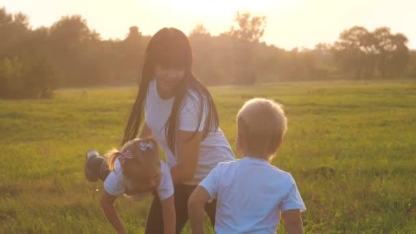 Boldog család vicces séta megy a kéz a kézben egy csapatmunka Silhouette. boldog kisgyerekek fiú és lány anya családi életmód naplementekor. anya és fia anya lánya és fia fehér pólóban