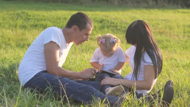šťastná rodinná týmová práce hrát smartphone sedět na trávě hrát zpomalený film. táta máma a dcera hrát na trávě přírody v životním stylu parku slunce legrační. otec holčička hrát digitální internet