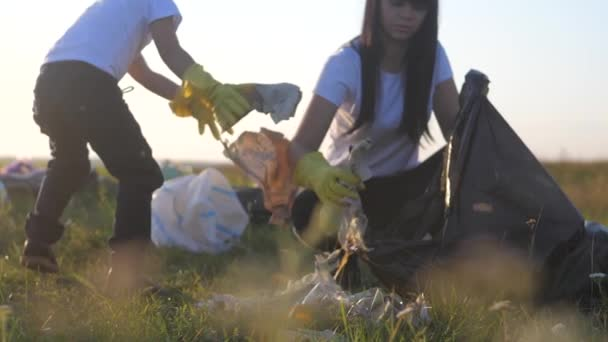 environmental teamwork a ecology teamwork volunteers awareness pollution household waste lifestyle concept. happy family group of people collects garbage plastic and paper waste bottles. children and