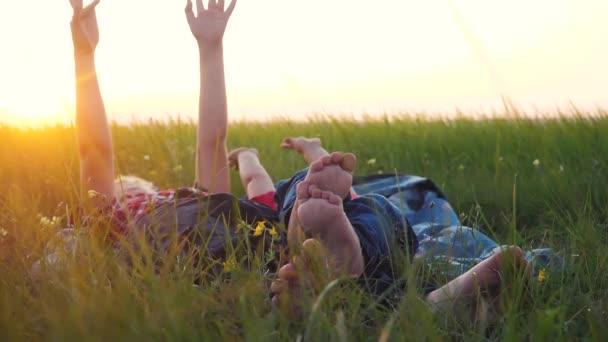 koncepce šťastných rodinných dětí. Děti s bosýma nohama ležet na trávě v parku na trávníku si odpočinout hrát bavte se. bratr a sestra přátelství bosé nohy životní styl relaxovat na trávě venku. málo