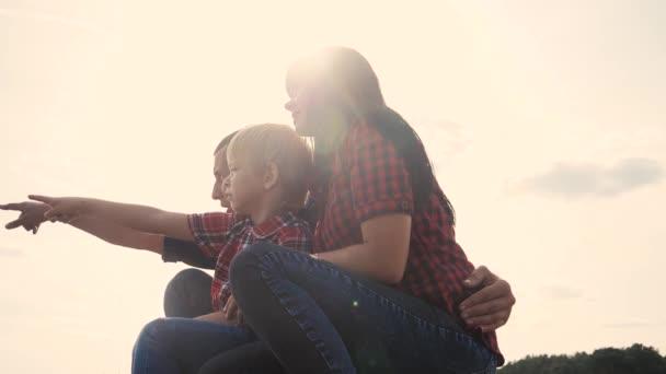 glücklich Familie Teamwork Konzept Zeitlupe Video. Papa Mama und Sohn Silhouette sitzen im Freien Sonnenuntergang Sonnenlicht. Vater Lifestyle Mann umarmt Mutter Mädchen und Sohn zeigt Hand in die Ferne eine glückliche Familie