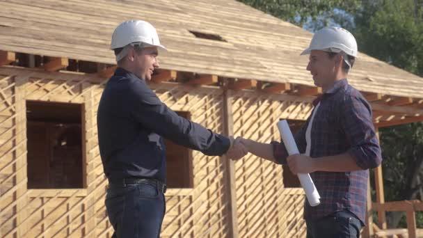 týmové práce s rukou. koncept stavba stavba architekt pomalý pohyb videa. dva muži stavitel v helmách potřese rukou firemní kontrast na staveništi. dva pracovníci v helmách se třesou