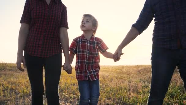 happy family concept go . mom dad and son a lifestyle walk in the park at sunset field in nature. happy family man girl and little boy slow motion video