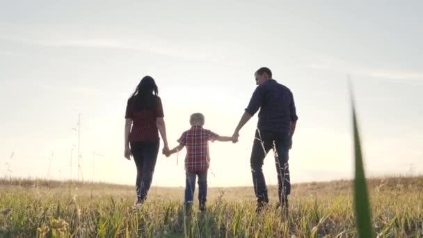 boldog család apa egy fiú és anya megy lassított videó koncepció. boldog csapatmunka apa férfi anya életmód lány és fiú fiú gyermek kéz a kézben járni a pályán a természetben. boldog család gondtalan gyermekkor