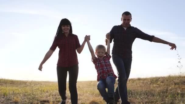 šťastný rodinný otec syn a máma běží zpomalit film zábavné video koncept. šťastný týmová práce táta muž maminka dívka a syn chlapec dítě běží držet ruce běh jít na poli životního stylu v přírodě. bezstarostný šťastný