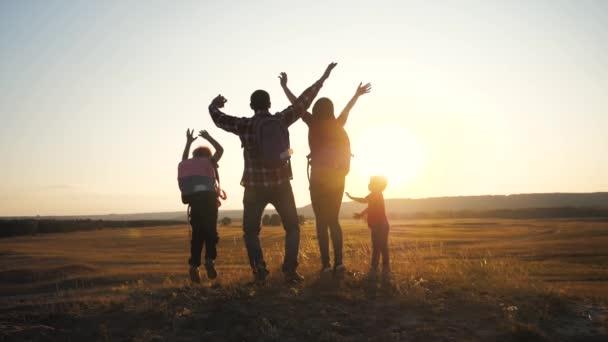lidé turisté týmová práce šťastná rodina s batohy skupina a pes silueta slunečního svitu turistů čtyři lidé stojí dosáhl vrcholu zvedl ruce na kopci na vrcholu západu slunce