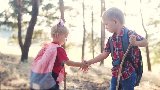šťastný rodinný malý chlapec a dívka turisté týmová práce handshake skauti turisté zpomalit video koncept. bratr a sestra turisté potřásají rukou s batohy turistiky v lese. skupina dětí