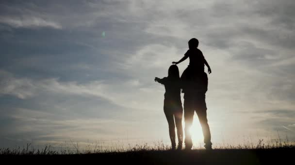 happy lifestyle family a teamwork Silhouette , happy children with mother and father , family at sunset .mom dad and son stand on the edge of a cliff of a hill watching the sunset silhouettes