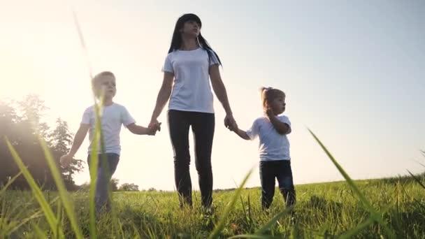 Šťastná rodina legrační chůzi jít za ruce týmová práce Silueta. šťastné děti malý chlapec a dívka s matkou rodiny při západu slunce. maminka a syn maminka dcera a životní styl syn v bílý trička