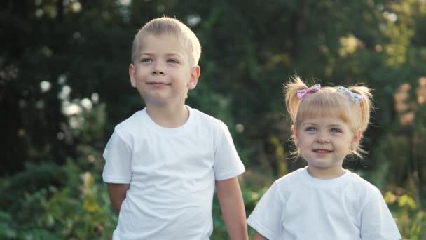 Šťastná rodina: malý chlapec a a životní styl dívka bratr a sestra držet za ruku na přírodě šťastný děti koncept. děti se na sebe dívají ve zpomalených filmech. dětské děti si hrají