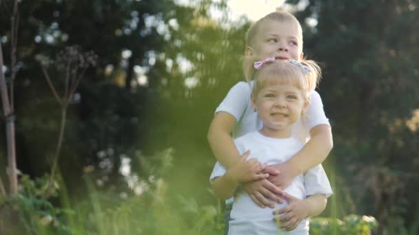 Šťastná rodina: malý chlapec objetí krouží objetí a dívka bratr a sestra držet ruku na přírodě šťastný děti koncept. děti se dívají jeden do druhého oči životní styl zpomalení videa. děti