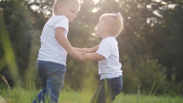 Boldog család: vicces lassított felvétel kisgyerek fiú kéz a kézben játszani örvény a és lány testvér és testvér tartsa a kezét a természet boldog gyerekek koncepciója. gyerekek boldog család életmód fiú lány lassú