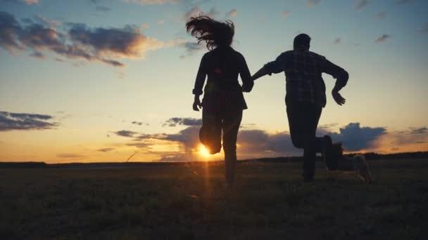 boldog család és kutya fut kezét naplementekor egy dombtetőn. koncepció csapat üzleti koncepció utazás szabadság győzelem boldogság csapatmunka. boldog család szülők kéz a kézben fut a napsugarak