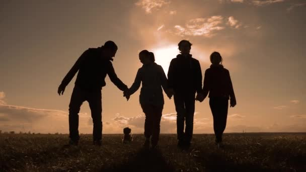 happy family and dog silhouette walking at sunset teamwork lifestyle. group of people friends walking holding hands slow motion video. Happy family party and pet teamwork concept