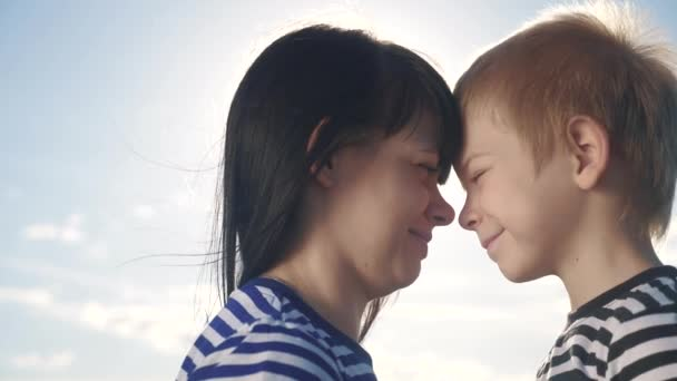 son and mom cute video concert mothers day. teamwork happy family boy kisses mother on the cheek touches his nose. parent takes care of the child. kid and adult woman mom in the sunlight at lifestyle