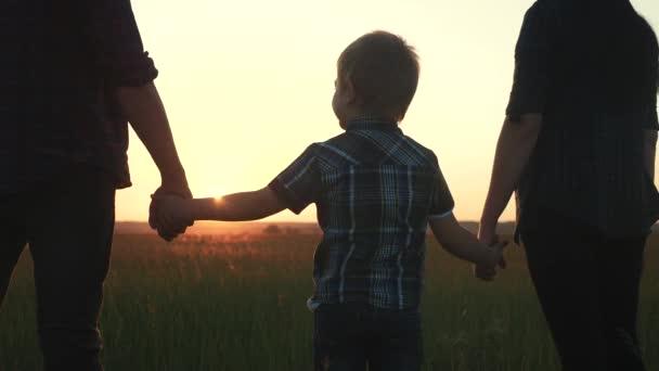 šťastná rodina mazlící se otec matka a syn držet ruku týmovou práci. Syn malý chlapec a táta máma stojí při západu slunce a dívají se na slunce. šťastný rodinný rodiče a dítě silueta životní styl
