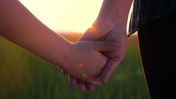 Glückliche Familienmütter und -söhne halten Händchen. Mutter und Junge Hand in Hand bei Sonnenuntergang. Eltern Mädchen und Kind glücklich Kindheit Lebensstil