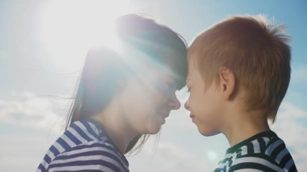 son and mom cute video concert mothers day. teamwork happy family boy kisses mother on the cheek touches his nose. parent takes care of the child. kid and adult lifestyle woman mom in the sunlight at