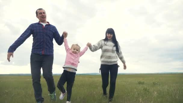 glückliche Familie. Mama Papa und kleines Kind laufen im Park und heben die Hände, spielen im Freien und halten die Hände. Frau und kleines Mädchen heben bei Sonnenuntergang die Hände auf der grünen Wiese