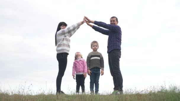 Šťastná rodina. Týmová práce Dospělí rodiče a malé děti ukazuje dům a symbol pohodlí. šťastný rodina maminka táta a děti děti vykreslit dům střecha držet jejich životní styl ruce nad hlavou
