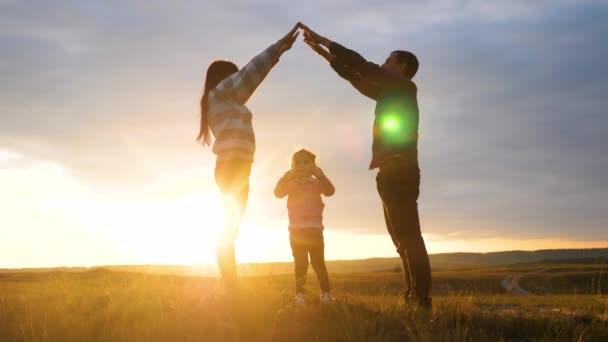 Šťastná rodina. Týmová práce Dospělí rodiče a malé děti ukazuje dům a symbol pohodlí siluetu při západu slunce. šťastný rodina maminka táta a děti děti vykreslit dům životní styl střecha držet ruce