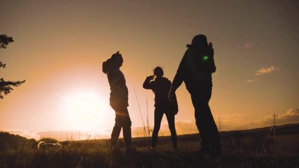 Teamwork-Business-Travel-Konzept gewinnen. glückliche Familie ein Team Mann, Frau und Kinder Sonnenuntergang Silhouette helfen, Hände zu schütteln Sieg Erfolg. Zeitlupenvideo. Tourismus Mann und Frau an der Spitze
