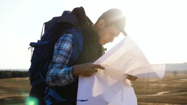 turistický cestovatel muž s papírovou mapou navigační hledá cestu na mapě. podnikatelský koncept svoboda cestování turistika dobrodružství. Hipster silueta životní styl slunce turista s batohem