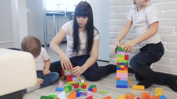 childhood happy family mom and children are playing concept little girl and boy brother and sister collects constructor teamwork. child plays toys sitting on floor. lifestyle children play in a team
