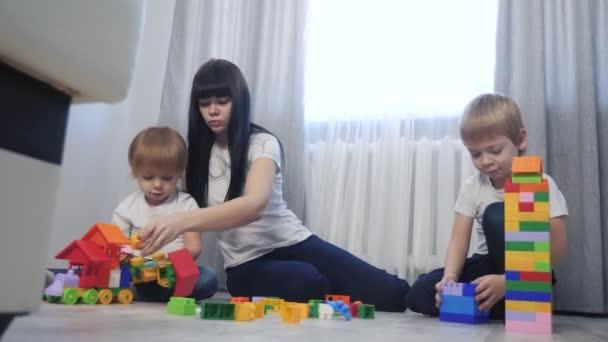 dětství šťastná rodina maminka a děti hrají koncept životního stylu holčička a chlapec bratr a sestra sbírá konstruktér týmová práce. dítě hraje hračky sedící na podlaze. děti si hrají v týmu
