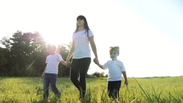 happy family teamwork mother, little brother and sister walk in the park nature holding hands slow motion video concept. mom, kids boy and lifestyle girl daughter and son hold hands go on green grass
