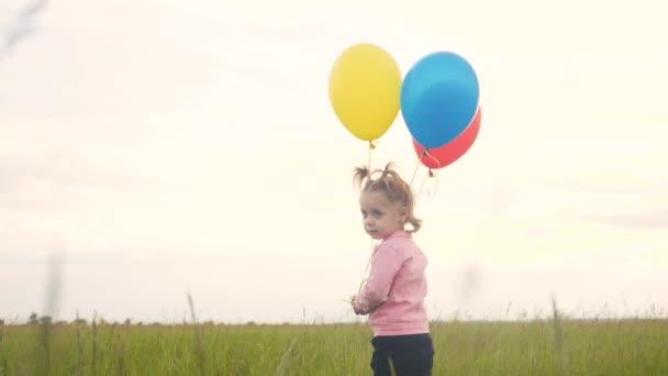 einsame Tochter kleines Mädchen mit Luftballons an ihrem Geburtstag. Glückliches Familienkonzept. trauriger Mädchentag. Kind und Luftballons vor blauem Himmel sorgen für eine glückliche Familie und Kindheit