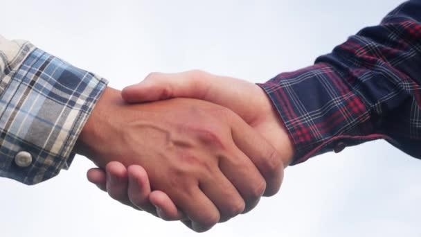 Koncept týmové práce. dva lidé si potřásají rukama. různé barvy pleti potřást rukou uzavřít obchodní smlouvu close-up. lidé různých barev pleti partnerství