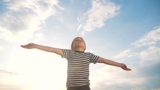 A fiú imádkozik, hogy az ég felé húzza a kezét, a kék ég felé. gyermek koncepció hit vallás és boldog család. A fiú oldalra teszi a kezét a kék égi zsidó ellen, aki Istenhez imádkozik. imádat és hála