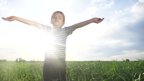 chlapec se modlí, táhne ruce k obloze proti modré obloze. dětský koncept víry náboženství a šťastný životní styl rodiny. synku, dej ruce na stranu proti modravému nebi a modli se k Bohu. uctívání a vděčnost