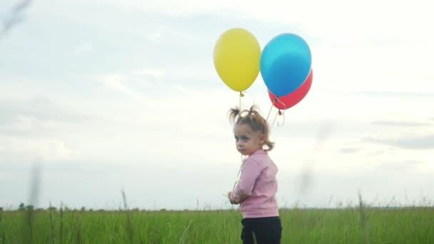 einsame Tochter kleines Mädchen mit Luftballons a an ihrem Geburtstag. Glückliches Familienkonzept. trauriger Mädchentag. Kind und Luftballons vor blauem Himmel sorgen für eine glückliche Familie und einen glücklichen Lebensstil
